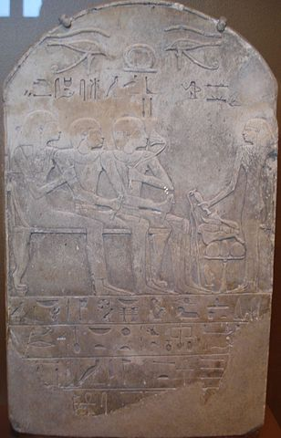 Funerary stele of a man named Ba sniffing a sacred lotus while receiving libations with his family member seated behind him